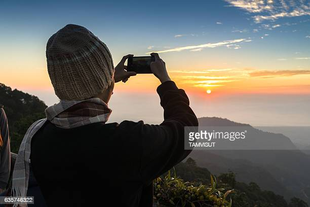 Man using smart phone take a photo sun rise at mountain view point.