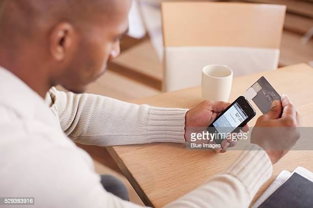 Man using smart phone to pay with credit card