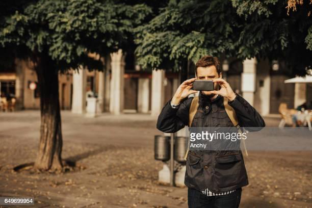Man using smart phone to take photos
