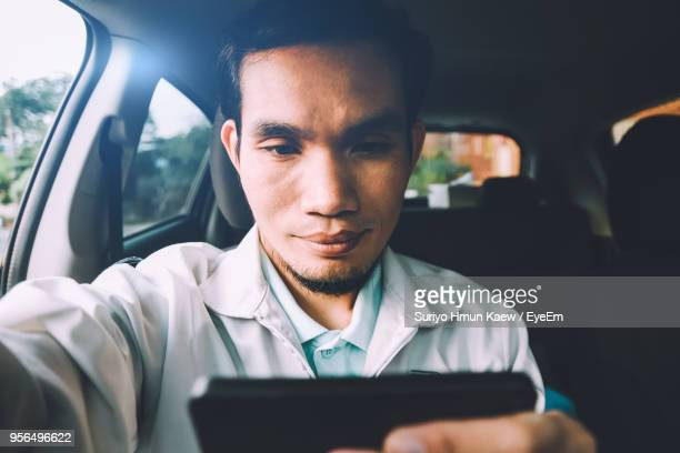 Man Using Smart Phone While Sitting In Car