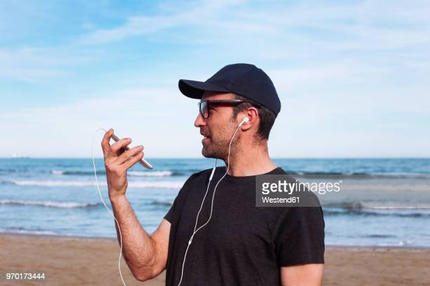 man using smartphone and earphones on the beach - bones - fotografias e filmes do acervo