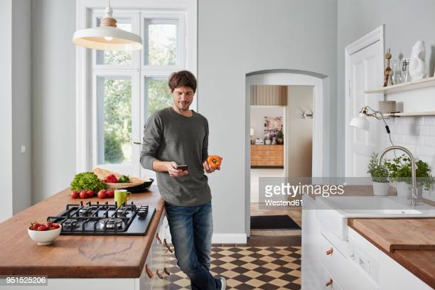 man using smartphone and holding bell pepper in kitchen - ein mann allein stock-fotos und bilder