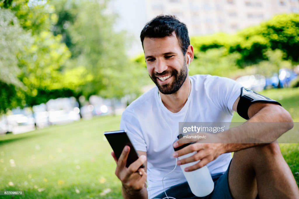 Man using smartphone and sitting in the park after training : Stock Photo