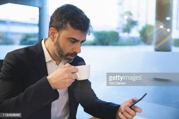 man using smartphone at a cafe - cris cantón photography stock pictures, royalty-free photos & images