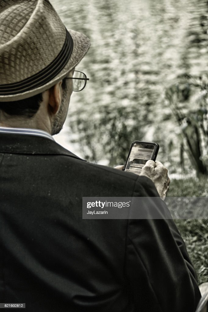 Man using Smartphone, holding device in front of him. : Stock Photo