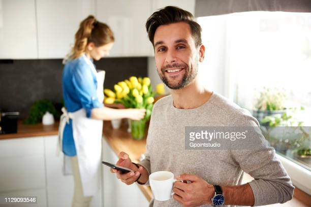 Man using smartphone in kitchen, woman arranging flowers in background