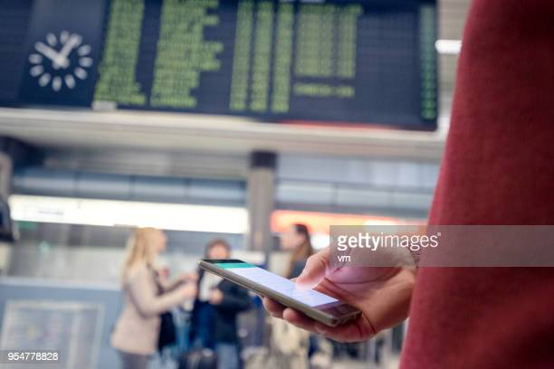 Man using smartphone near airport timetable