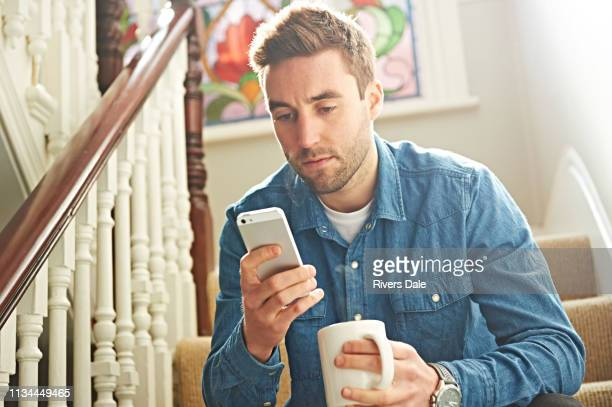 man using smartphone on stairs - worried stock pictures, royalty-free photos & images