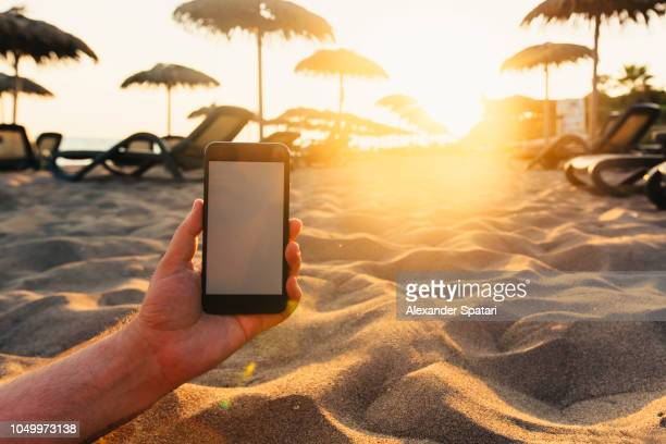 Man using smartphone on the beach lying on the sand during sunset, personal perspective