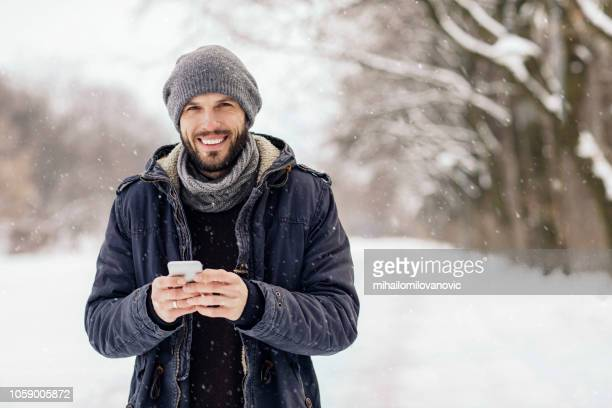 man using smartphone - inverno foto e immagini stock