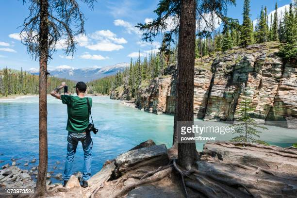 Man Using Smartphone to Photograph the Athabasca River in the Canadian Rocky Mountains of Jasper National Park, Alberta, Canada