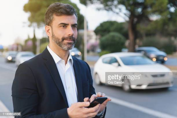 man using smartphone to request pickup by taxi - cris cantón photography fotografías e imágenes de stock