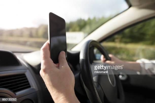 Man using smartphone whilst driving. Internet addicted