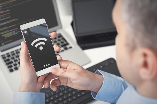 Man using smartphone with wireless symbol 1131624481