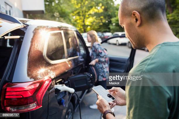 man using smartphone with woman standing by car in background - elektroauto stock-fotos und bilder