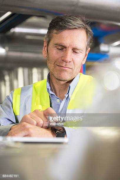Man using smartwatch in industrial plant