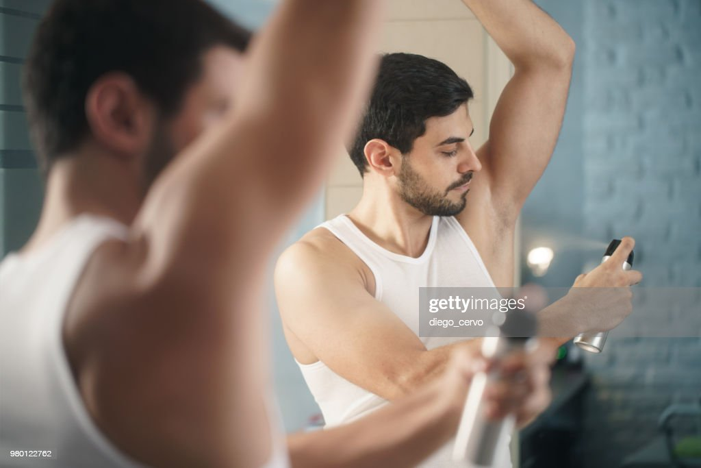 Man Using Spray Deodorant On Underarm For Bad Smell : Stock Photo