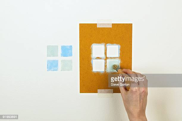 man using stencil and paintbrush to create pattern on wall - stencil stock pictures, royalty-free photos & images