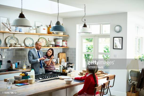 man using tablet and discussing with woman in family kitchen - routine stock pictures, royalty-free photos & images