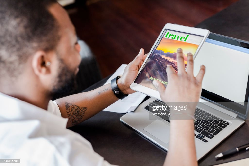 Man using tablet at desk in home office : Stock Photo
