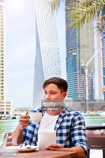 Man using tablet computer in cafe in Dubai Marina