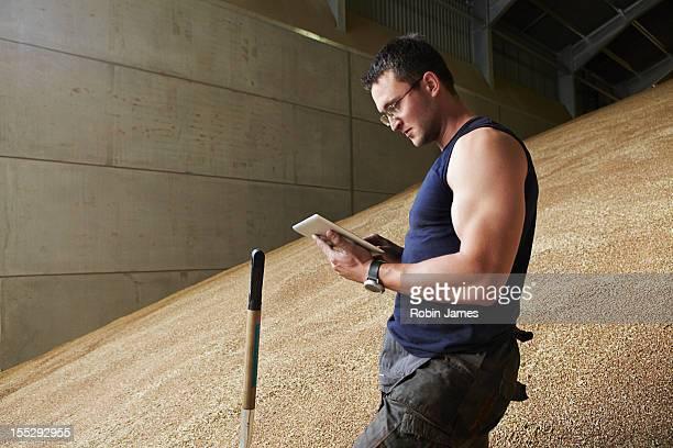 Man using tablet computer in grain