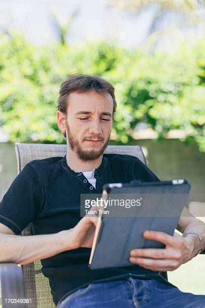 Man using tablet computer in the backyard
