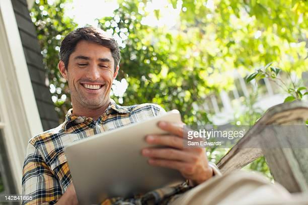 man using tablet computer outdoors - schrägansicht stock-fotos und bilder