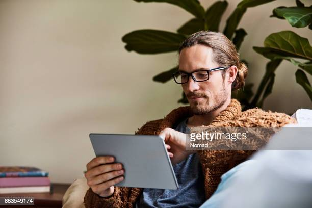 Man using tablet computer while sitting on sofa