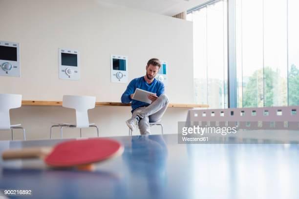 Man using tablet in break room of modern office