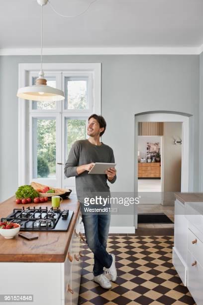 man using tablet in kitchen looking at ceiling lamp - ajustar imagens e fotografias de stock