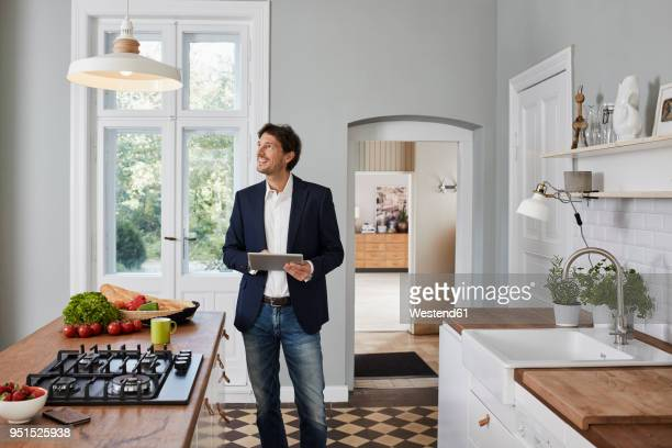 man using tablet in kitchen looking at ceiling lamp - anzugjacke stock-fotos und bilder