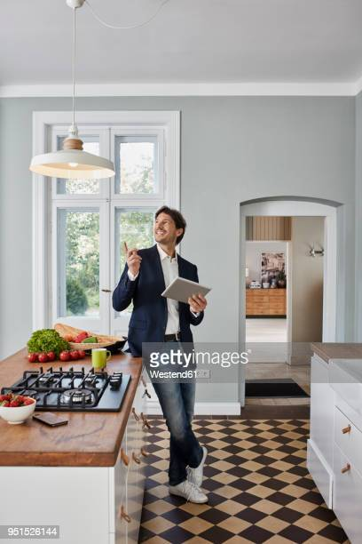 man using tablet in kitchen looking at ceiling lamp - remote controlled stock photos and pictures