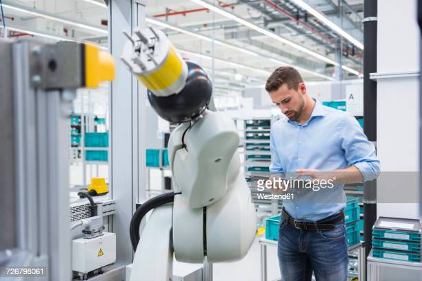man using tablet nextb to assembly robot in factory shop floor - industriebetrieb stock-fotos und bilder