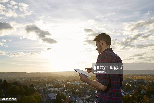 Man using tablet on a hill above a town