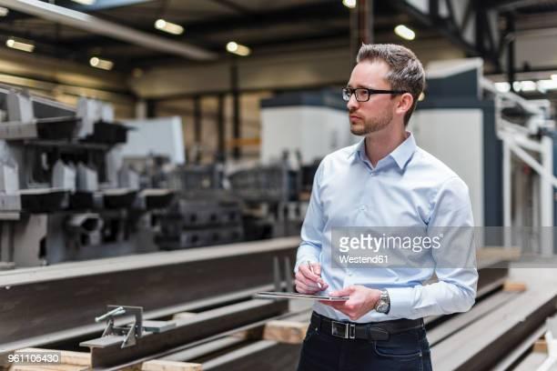 man using tablet on factory shop floor - computeronderdeel stockfoto's en -beelden