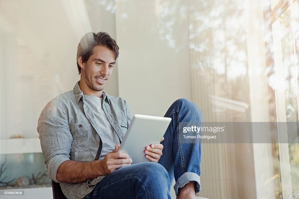 Man using tablet pc at home : Bildbanksbilder