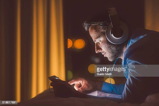 man using tablet pc in evening. - music stock-fotos und bilder