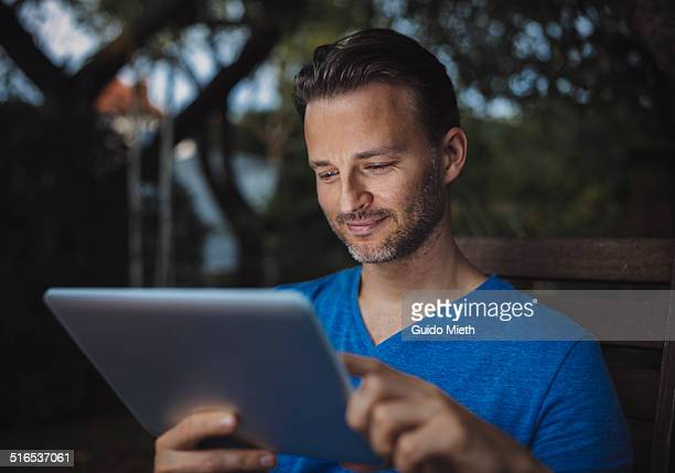 Man using tablet pc in garden.