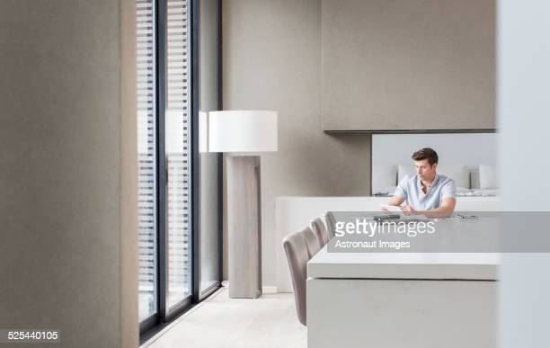 Man using tablet pc in modern dining room
