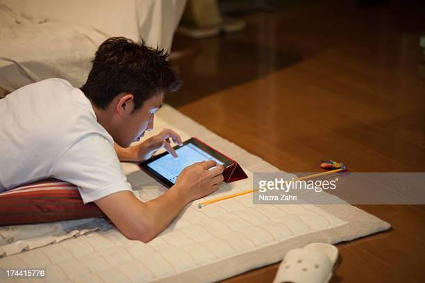 man using tablet pc on the floor - 腹ばい ストックフォトと画像
