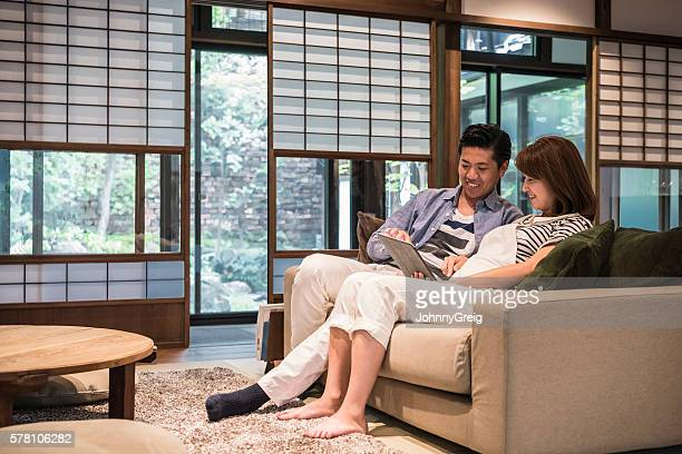 Man using tablet sitting on sofa with pregnant woman