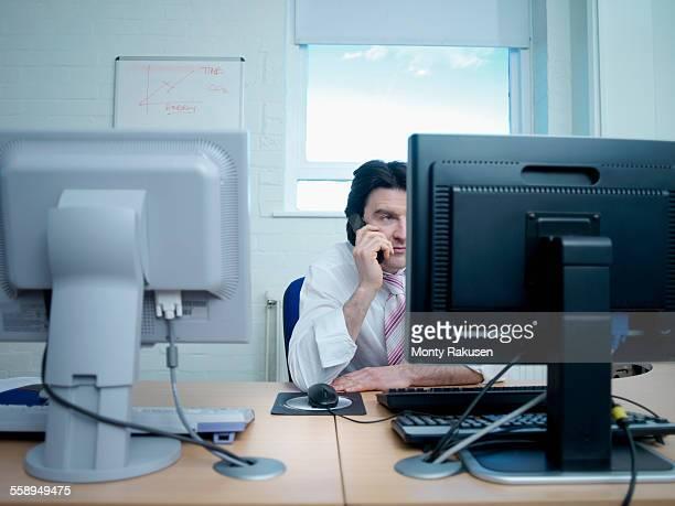 man using telephone and working on computer at desk - monty rakusen stock-fotos und bilder