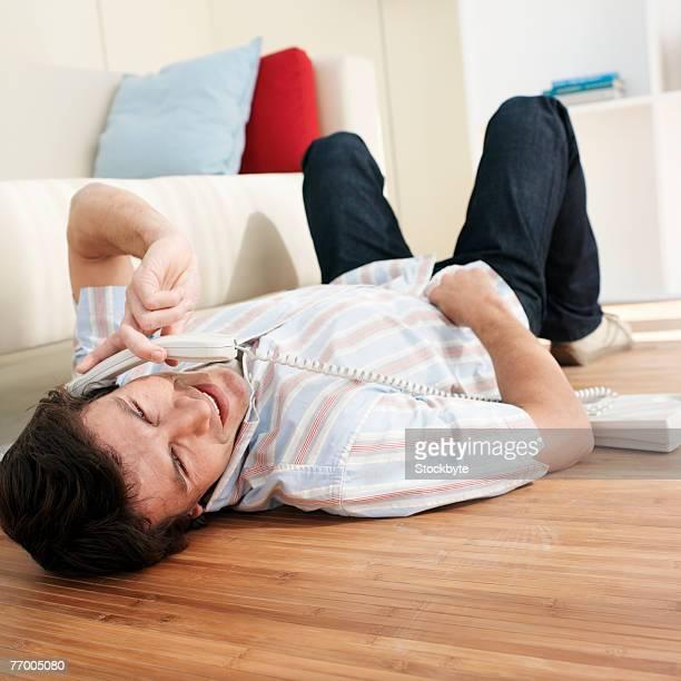 man using telephone, lying on living room floor - sdraiato foto e immagini stock