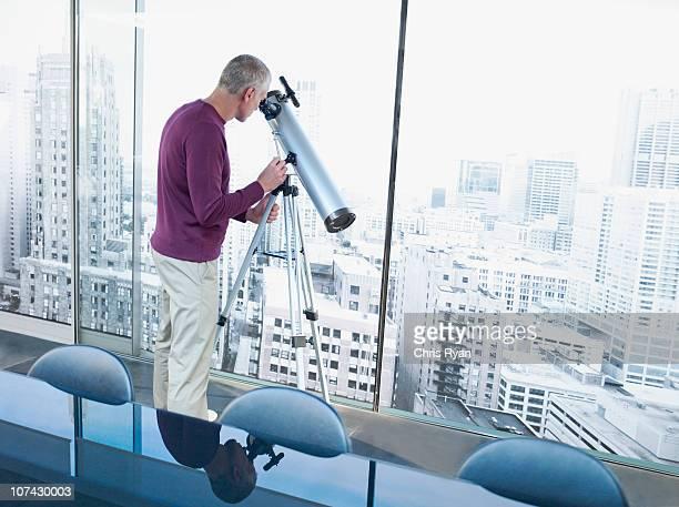 男性に望遠鏡で、街の建築物