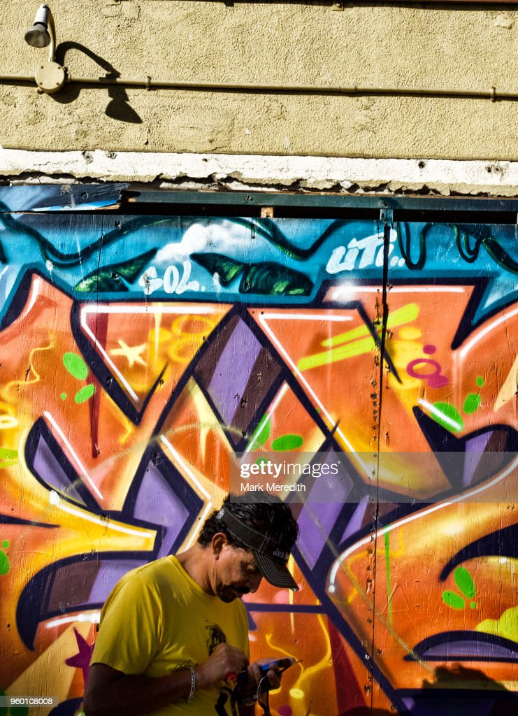 Man using texting on a mobile phone by a Venice Beach mural : Stock-Foto