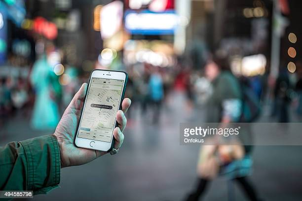 man using the uber taxi app on iphone in nyc - navigational equipment stock pictures, royalty-free photos & images