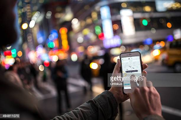 man using the uber taxi app on iphone in nyc - mobil brand name stock pictures, royalty-free photos & images