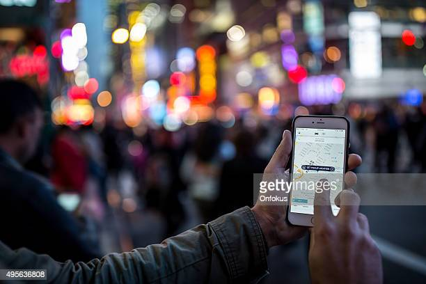 Mann mit der Uber-App für Iphone Taxi in New York City