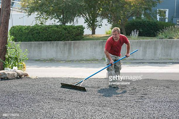 Man using tool to smooth asphalt on new driveway
